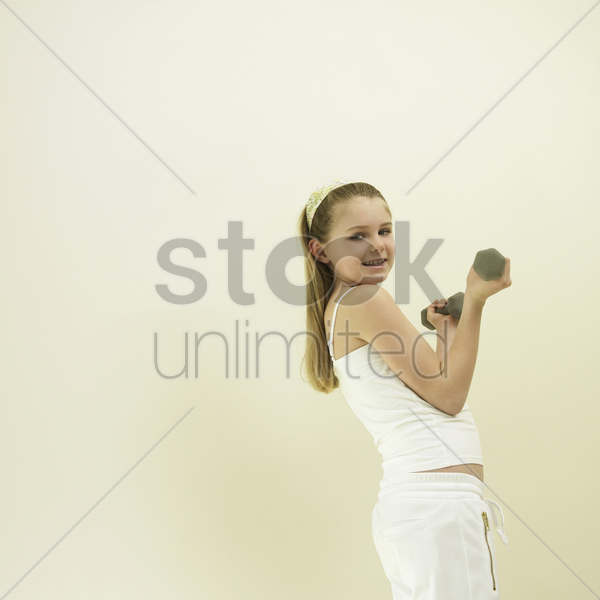 little girl lifting dumbbell stock photo