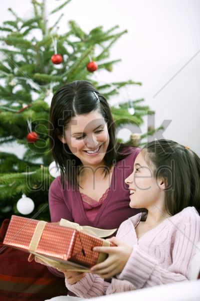 little girl receiving a christmas present from her mother stock photo
