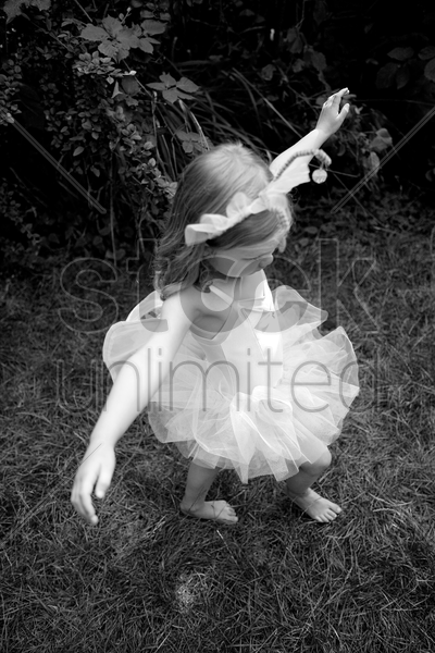 little girl wearing ballet dress dancing happily stock photo