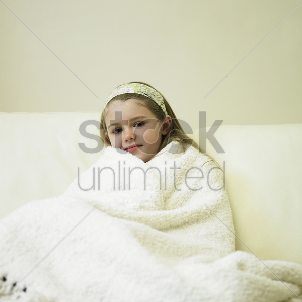 little girl wrapped in blanket sitting on couch stock photo