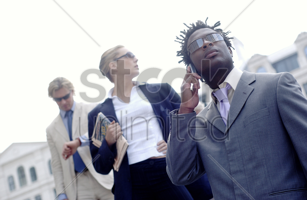 low angle shot of three working people in working attire standing diagonally on the stairs stock photo