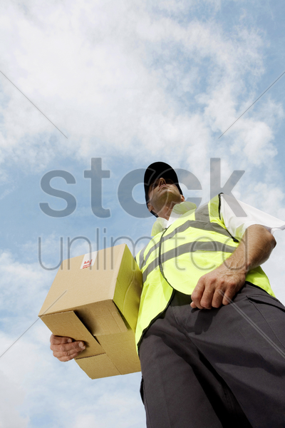 low angle view of a delivery man carrying a box stock photo