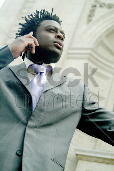 low angle view of a man in business suit making a call from his hand phone stock photo