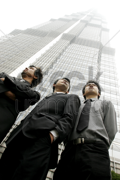 low angle view of three businessmen standing in front of the building stock photo