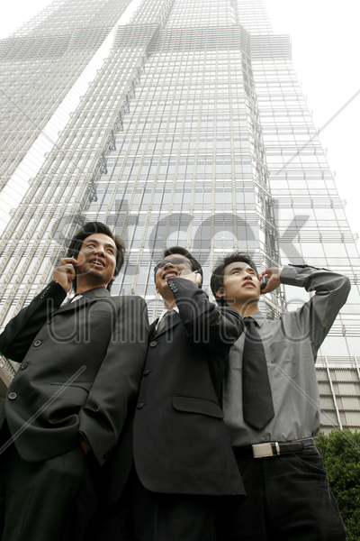 low angle view of three businessmen talking on the hand phones stock photo