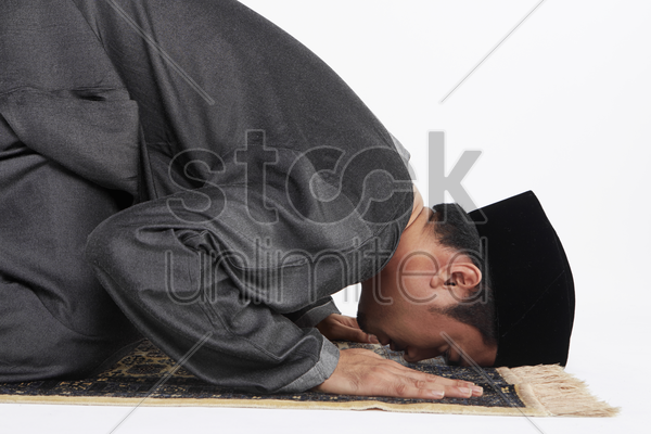 main kneeling and staying prostrate by pressing forehead, and placing palms, knees and pads of the toes on the floor. stock photo