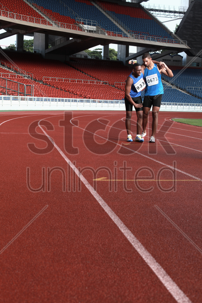 male athlete helping another injured athlete stock photo
