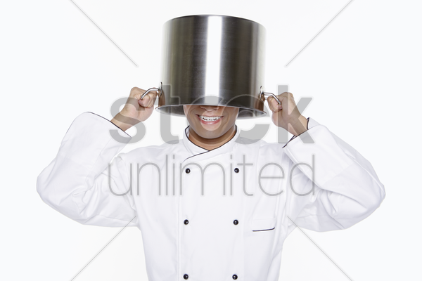 male chef covering his head with a pot stock photo