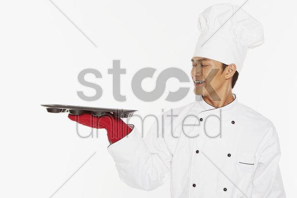 male chef holding a baking tray stock photo
