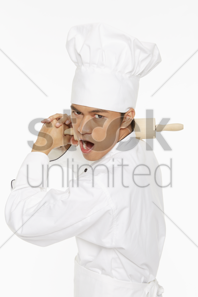 male chef holding a rolling pin, showing hitting gesture stock photo