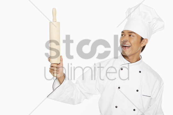 male chef holding up a rolling pin stock photo
