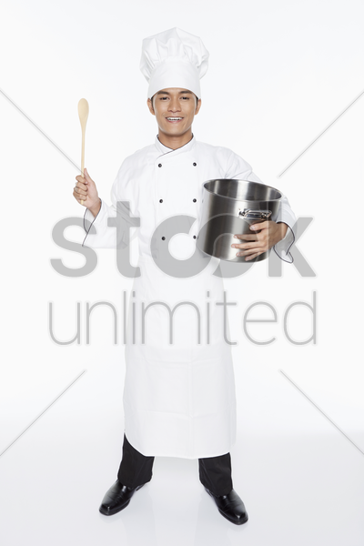 male chef holding up a wooden spoon and a pot stock photo