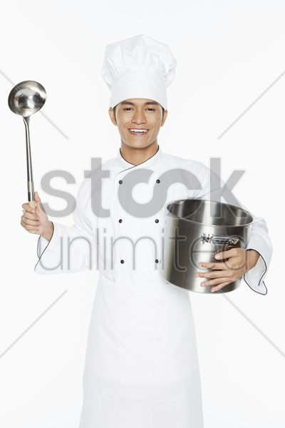 male chef holding up ladle and pot stock photo