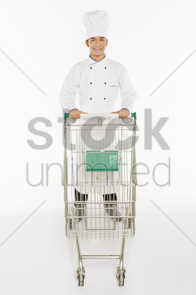 male chef pushing a shopping cart stock photo