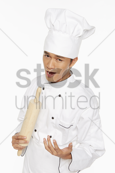 male chef singing into a rolling pin stock photo