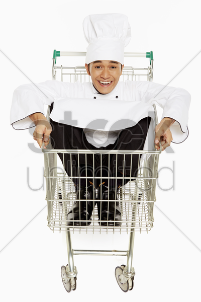 male chef sitting inside a shopping cart stock photo
