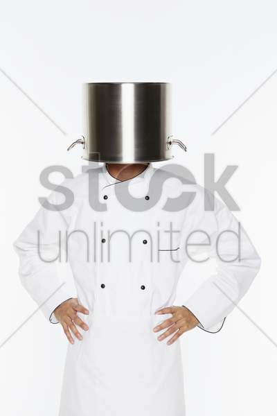 male chef standing with pot covering his head stock photo