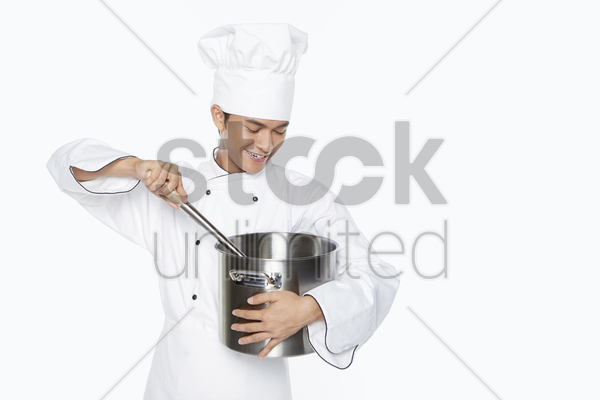 male chef stirring food in the pot stock photo