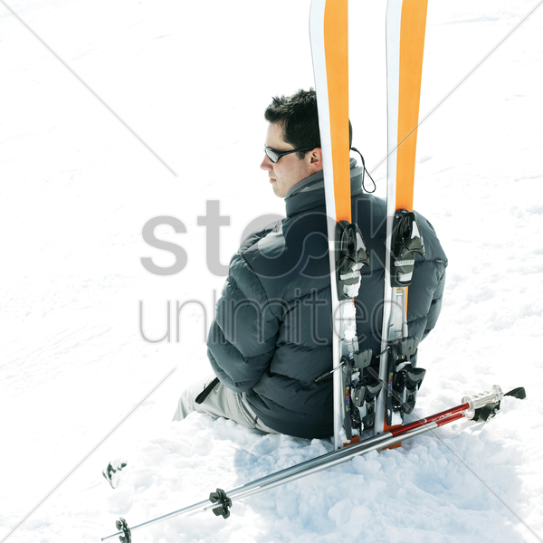 male skier sitting with his skis and ski poles stock photo