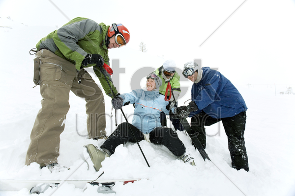male skiers helping a female skier to stand up stock photo