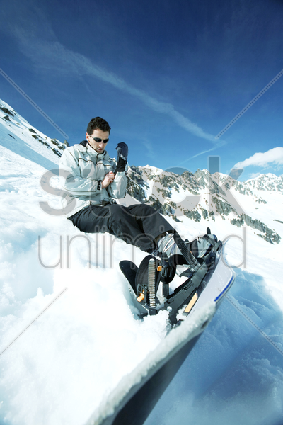 male snowboarder adjusting his glove stock photo
