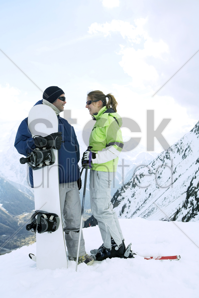 male snowboarder and female skier stock photo