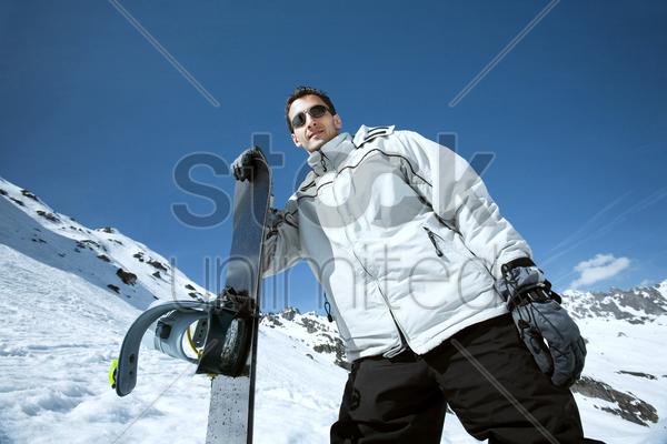 male snowboarder posing for the camera stock photo