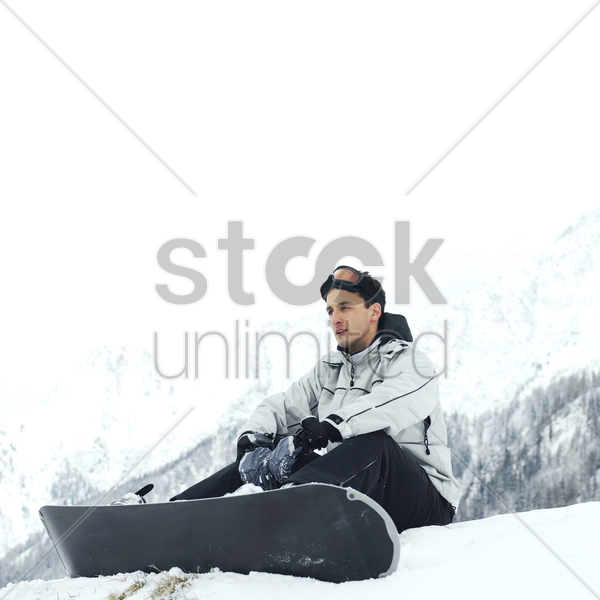 male snowboarder sitting alone stock photo