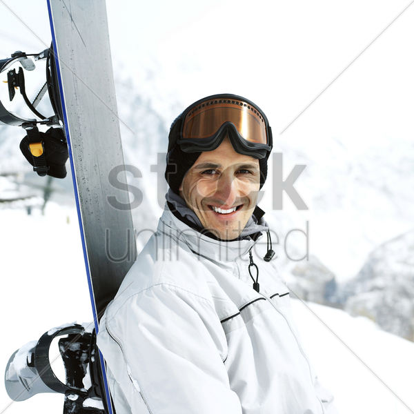 male snowboarder smiling at the camera stock photo