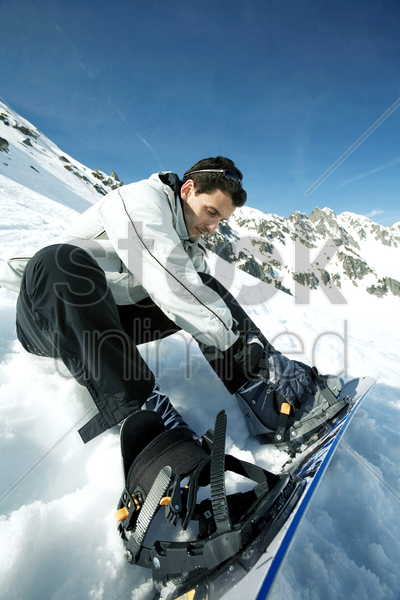 male snowboarder strapping board onto feet stock photo