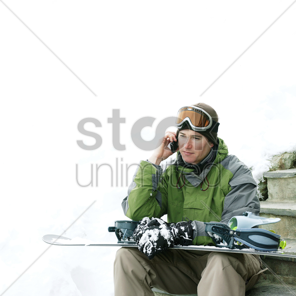 male snowboarder talking on the phone stock photo