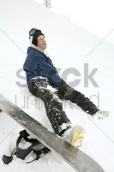male snowboarder with injured leg stock photo