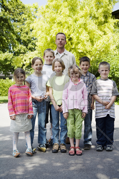 male teacher posing with his students stock photo