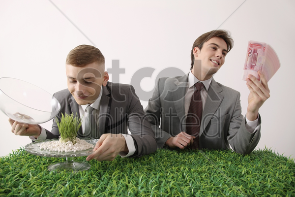man admiring grass seedling while another man is admiring money stock photo