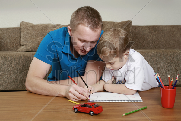man and boy drawing on notebook stock photo