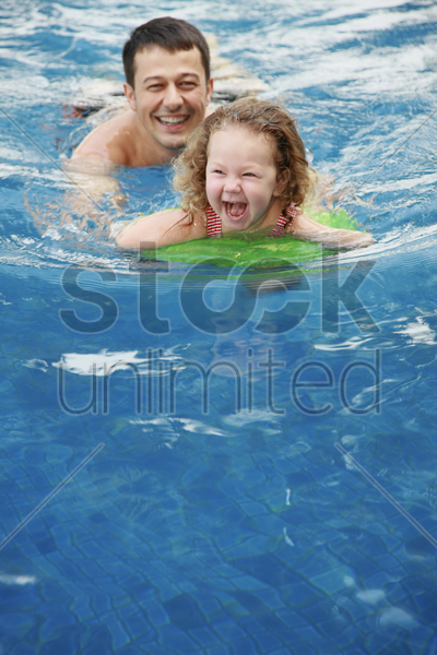 man and daughter swimming in the pool stock photo