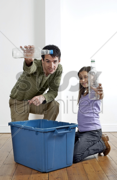 man and girl holding up plastic bottles to be recycled stock photo