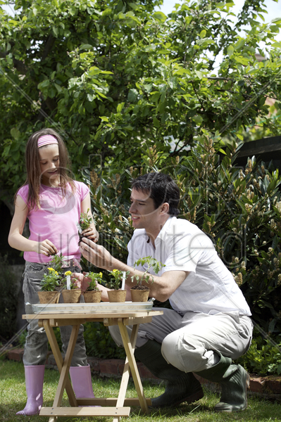 man and girl planting pots of flowers stock photo