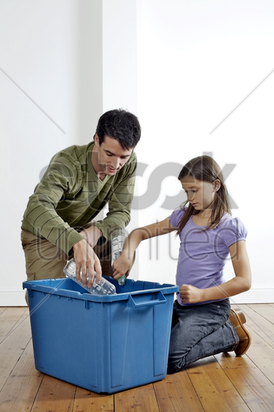 man and girl putting plastic bottles into a recycling container stock photo