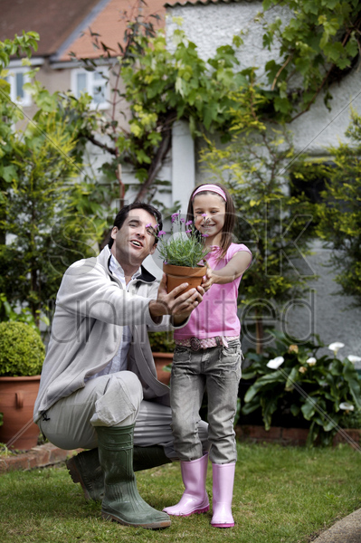man and girl showing a pot of flowers stock photo