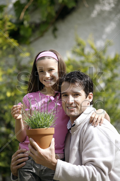 man and girl with a pot of flowers stock photo