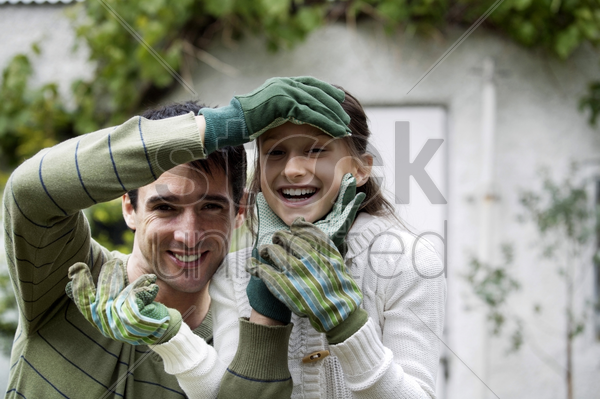 man and girl with gardening gloves stock photo