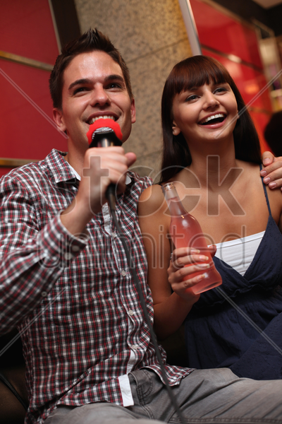 man and woman at karaoke bar stock photo