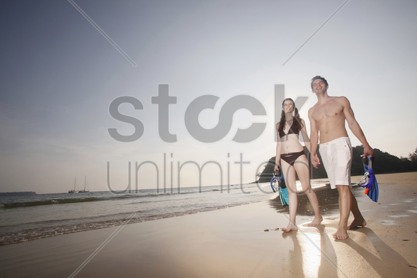 man and woman carrying snorkeling gear stock photo