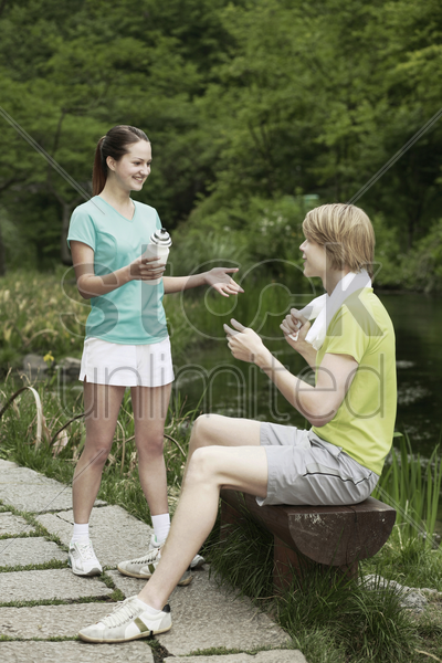 man and woman chatting in the park stock photo