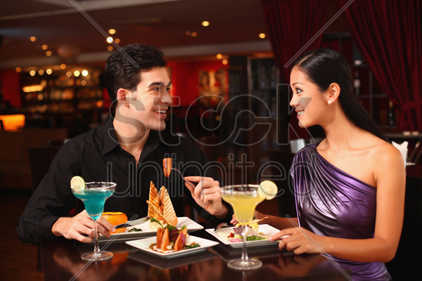 man and woman chatting while having dinner together stock photo