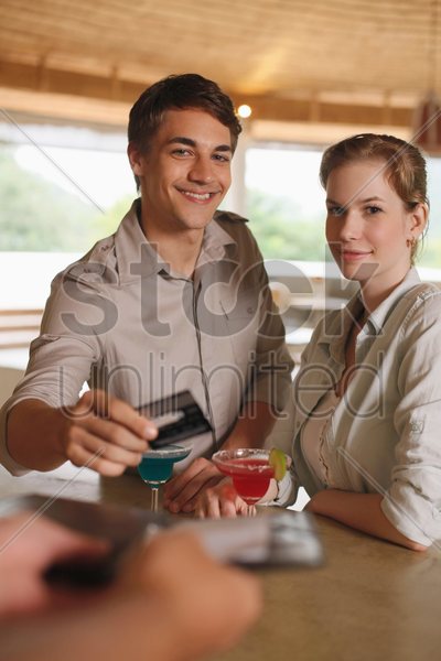 man and woman drinking at the bar, man paying for the drinks stock photo