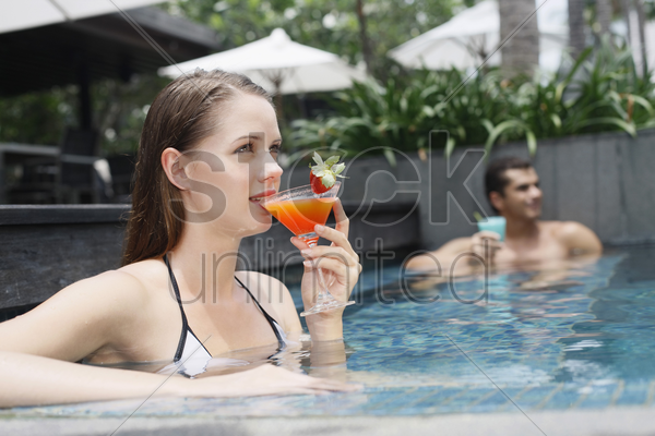 man and woman drinking while relaxing in the pool stock photo