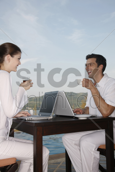 man and woman drinking while using laptop stock photo
