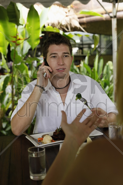 man and woman eating at a cafe, man talking on the phone stock photo